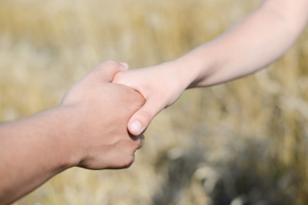Young couple's hands holding to each other over yellow background outdoors